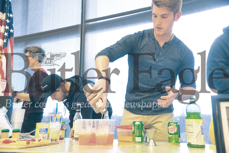 "Slippery Rock University junior Luke Everett, 22, pours his non-alcoholic mixed beverage called ""The Godfather"" into clear cups at the university's Alcohol Free Mix-Off. Photo by Gabriella Canalas"