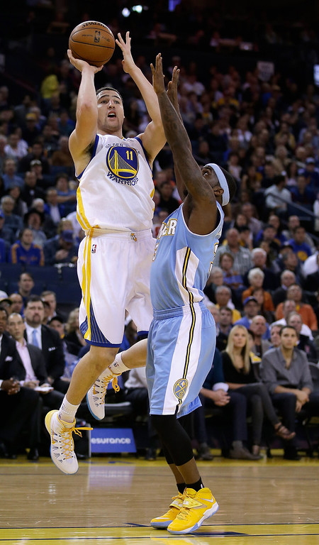 . Klay Thompson #11 of the Golden State Warriors shoots over Ty Lawson #3 of the Denver Nuggets at ORACLE Arena on January 15, 2014 in Oakland, California.  (Photo by Ezra Shaw/Getty Images)