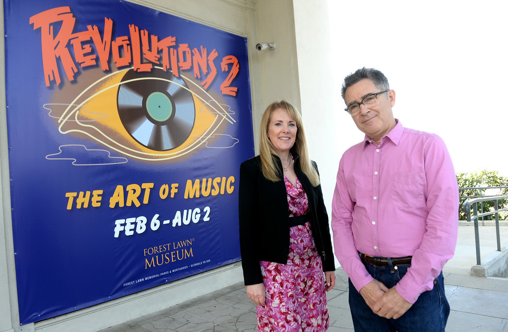 """. Forest Lawn Museum Director Joan P. Adan, left, with Artist Michael Doret during \""""Revolutions 2\"""" exhibit of photographs, posters and other art in music of the 1960s-1980s. More than 175 artworks by more than 35 artists will be on display, such as Black Sabbath album art to Jimi Hendrix Experience\'s concert posters in the Forest Lawn Museum at Forest Lawn Memorial Park in Glendale, Calif., on Tuesday, February 17, 2015. (Photo by Keith Birmingham/ Pasadena Star-News)"""