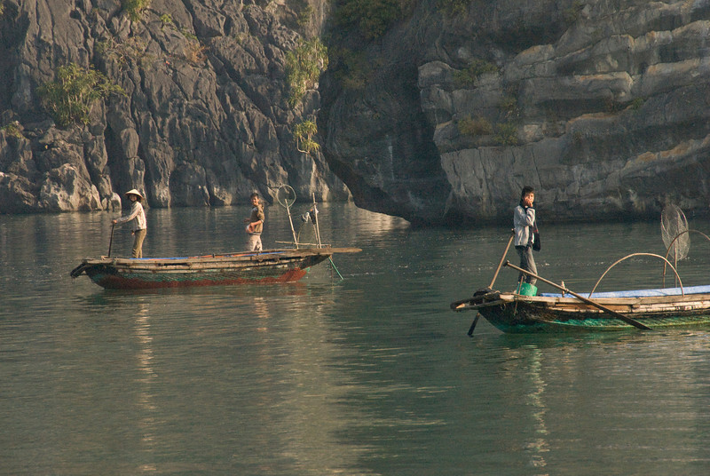 Fishermen on boats in Ha Long Bay, Vietnam