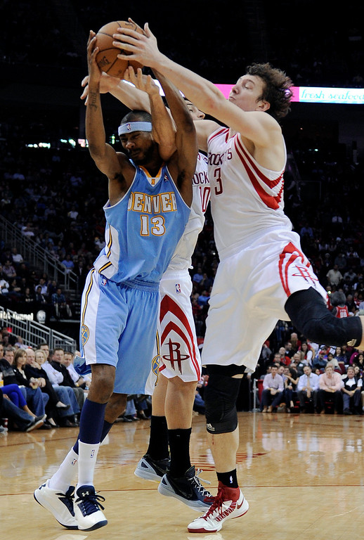 . Denver Nuggets\' Corey Brewer (13) is fouled by Houston Rockets\' Omer Asik (3) as Rockets\' Carlos Delfino (10) is caught in the middle during the second half of an NBA basketball game Wednesday, Jan. 23, 2013, in Houston. Denver won 105-95. (AP Photo/Pat Sullivan)