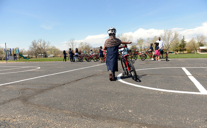 . Bahsan Aweys, 6, brings her new bike to join the rest of her classmates at Sable Elementary in Aurora, May 14, 2013. Panera Bread and Wish for Wheels, a local non-profit, donated 140 new bikes to benefit area kindergarteners around Denver. (Photo By RJ Sangosti/The Denver Post)