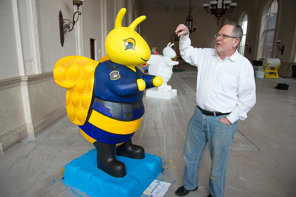 04/30/19 Wesley Bunnell | Staff Project Manager Stephen Hard of the Bees Across New Britain art event points out details on a bee which is painted by Martha Williams for the New Britain Police Department at the project headquarters at 55 West Main St on Tuesday afternoon.