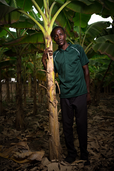 Farmer Adams proudly poses next to one of his plantain trees. Adams is another farmer that benefits from the UOWIAP project.