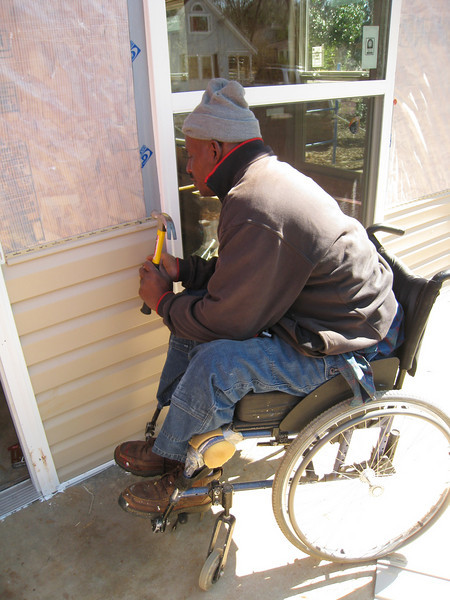 10 02-03  Thad Harris is happy to see siding going up on his house. ff