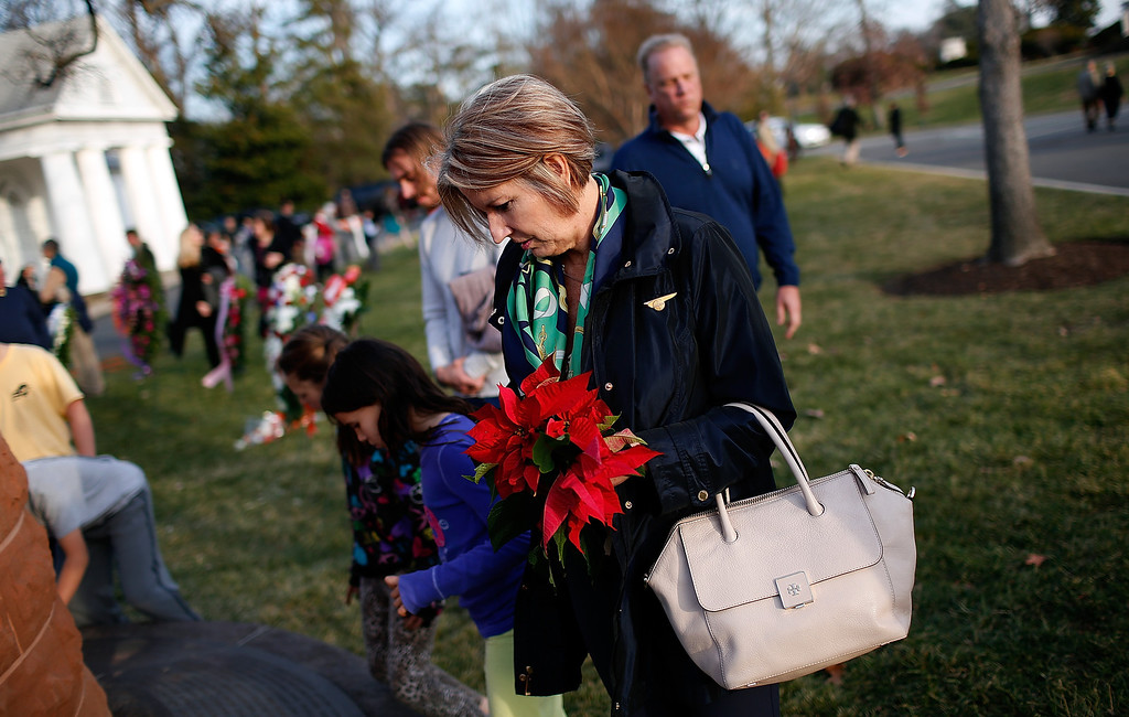 . Family members place flowers at the base of a cairn following a remembrance ceremony for those who died on Pan Am Flight 103 at Arlington National Cemetery December 21, 2013 in Arlington, Virginia.  (Photo by Win McNamee/Getty Images)