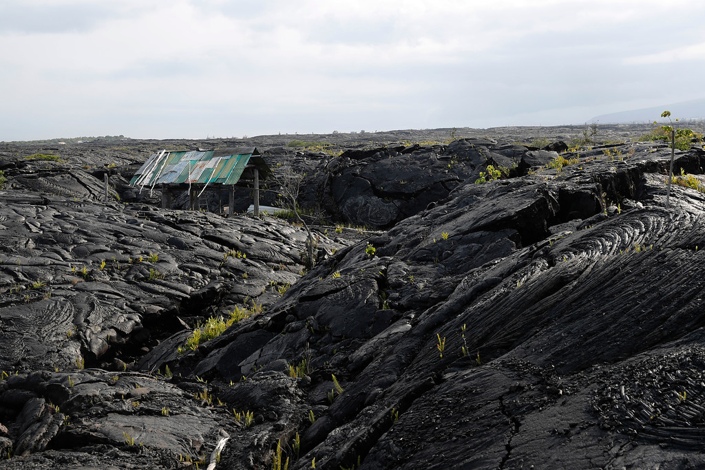 . A structure is seen atop the 1990 lava flow from Kilauea, one of the world\'s most active volcanoes, Sunday, May 6, 2018, in Kalapana, Hawaii. Kilauea has been erupting continuously since 1983. In 1990, when lava poured into Kalapana on the Big Island\'s southern coast, parked cars lined the roads and people crowded in to watch. Kilauea hasn\'t been the kind of volcano that shoots lava from its summit into the sky, causing widespread destruction. It tends to ooze lava from fissures in its sides. (AP Photo/Marco Garcia)