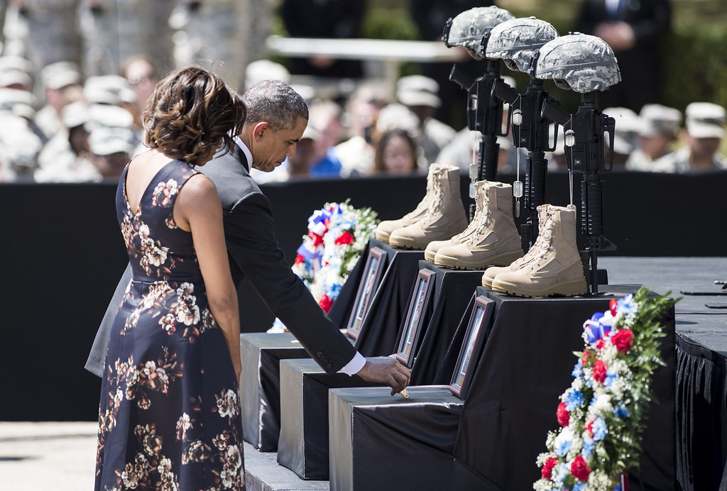 . US President Barack Obama and First Lady Michelle Obama pay their respects during a memorial service at Fort Hood April 9, 2014 in Texas. AFP PHOTO/Brendan SMIALOWSKI/AFP/Getty Images
