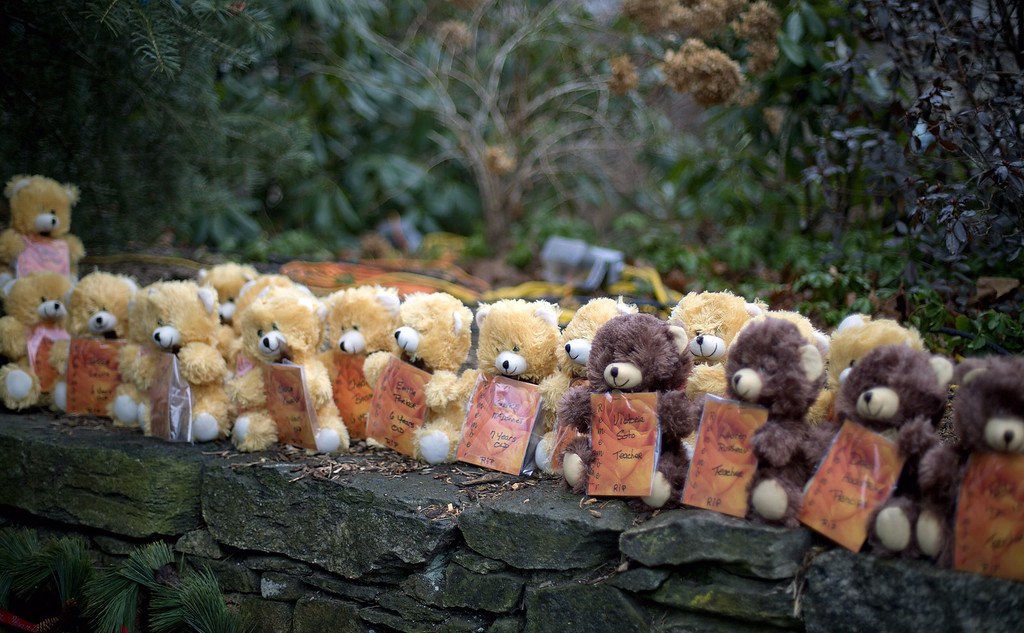 . Teddy bears, each representing a victim of the Sandy Hook Elementary School shooting, sit on a wall at a sidewalk memorial, Sunday, Dec. 16, 2012, in Newtown, Conn. A gunman walked into Sandy Hook Elementary School in Newtown Friday and opened fire, killing 26 people, including 20 children. (AP Photo/David Goldman)