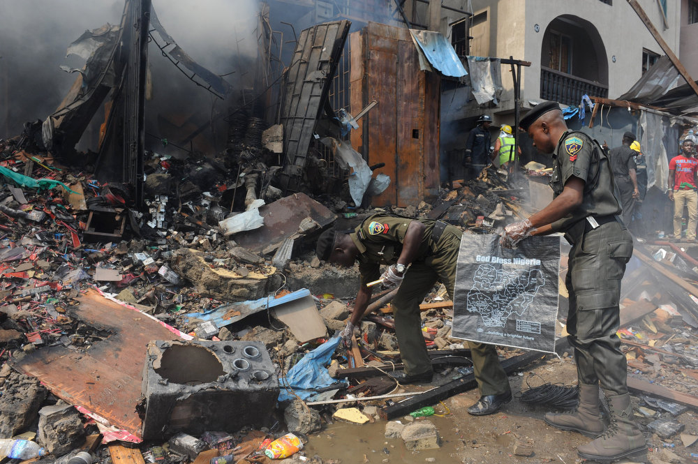 Description of . Anti-bomb policemen collect particles for examination at the scene of an explosion in a building in Lagos on December 26, 2012. Fire ripped through a crowded neighborhood in Nigeria's largest city and wounded at least 30 people after a huge explosion rocked a building believed to be storing fireworks, officials said.  AFP PHOTO/PIUS UTOMI EKPEI/AFP/Getty Images