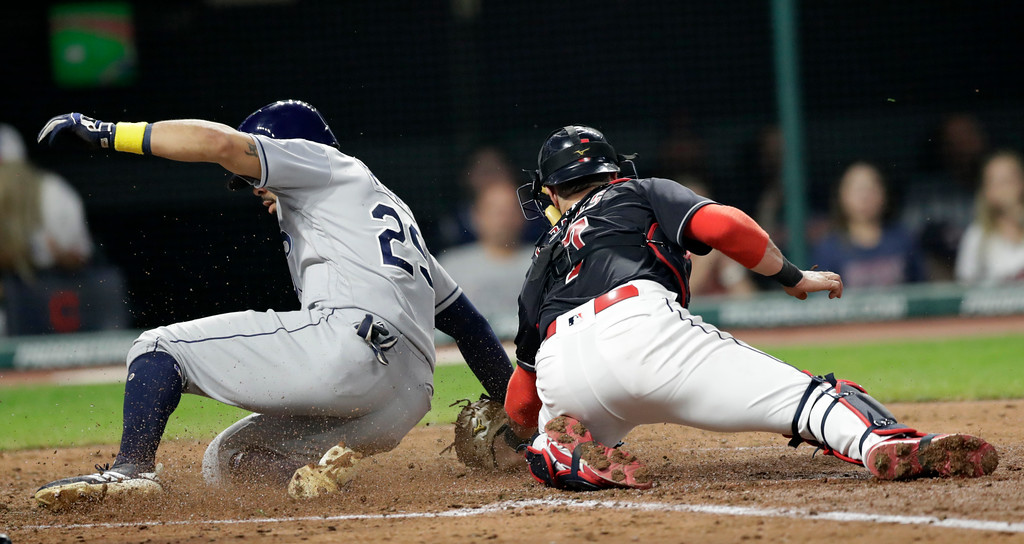 . Tampa Bay Rays\' Tommy Pham slides safely into home plate as Cleveland Indians\' Yan Gomes is late on the tag in the sixth inning of a baseball game, Saturday, Sept. 1, 2018, in Cleveland. (AP Photo/Tony Dejak)