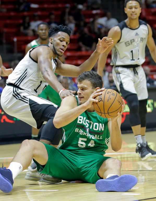 . Boston Celtics center Ante Zizic (54) passes the as San Antonio Spurs forward Jaron Blossomgame, left, defends during the first half of an NBA summer league basketball game Wednesday, July 5, 2017, in Salt Lake City. (AP Photo/Rick Bowmer)