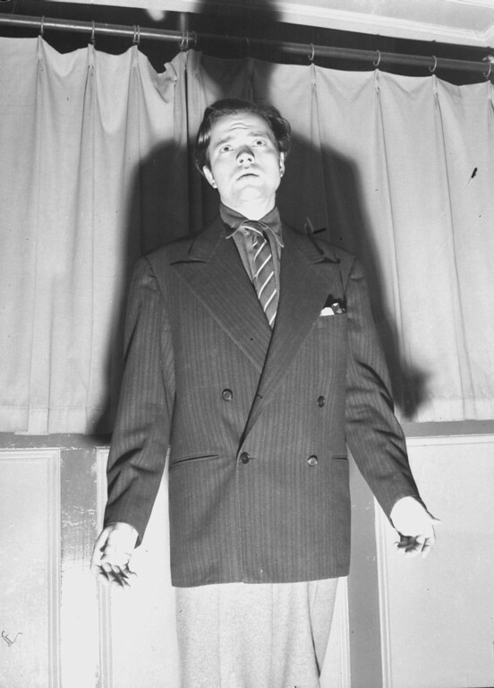 """. Orson Welles is shown putting out his hands after his CBS radio broadcast over a national hookup October 30, 1938, which dramatized an H.G. Wells novel called \""""War of the Worlds,\"""" was interpreted by listeners as an actual news broadcast of an invasion of New Jersey by men from Mars who began to lay waste to the countryside with fabulous weapons.  The whole country was thrown into an uproar by the broadcast.  In Newark, N.J., 15 persons were wounded when they attempted to flee the \""""attack.\""""  (AP Photo)"""