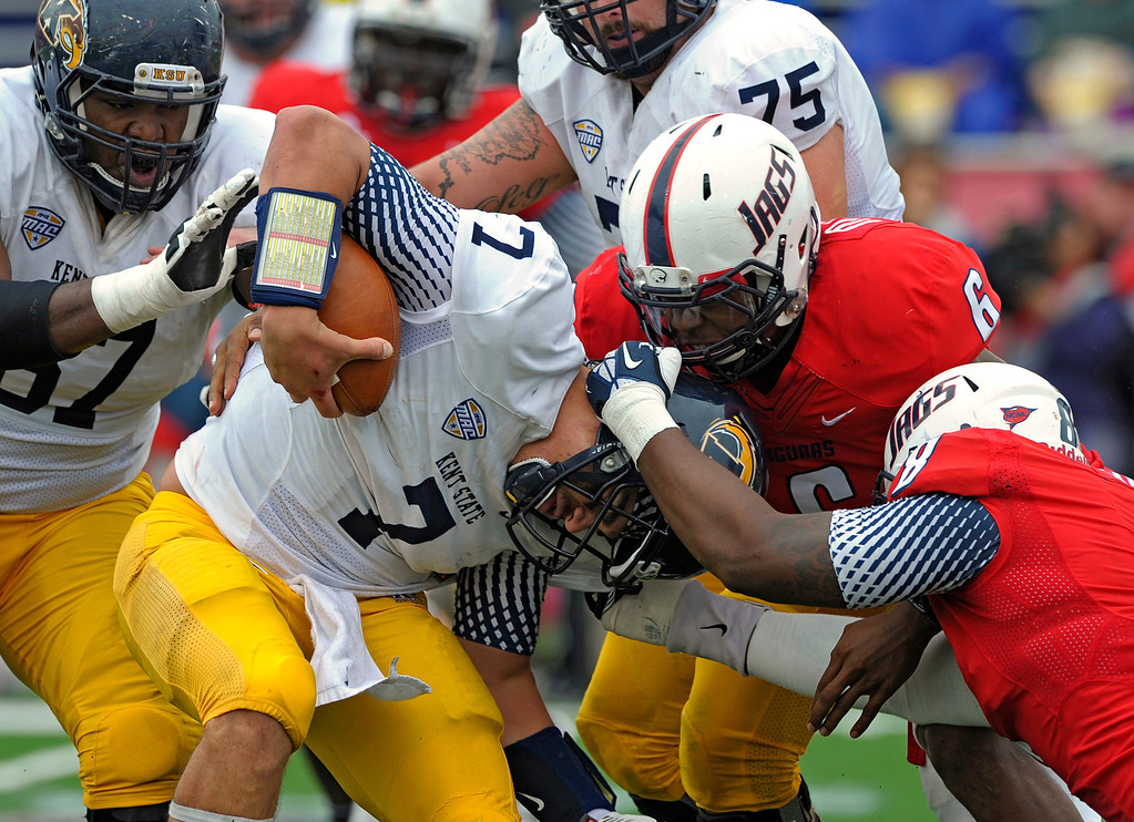 . Kent State quarterback David Fisher (7) is tackled by South Alabama linebacker Maleki Harris (6) and defensive end Pat Moore (8) in the second quarter of an NCAA college football game in Mobile, Ala., Saturday, Oct. 19, 2013. (AP Photo/G.M. Andrews)