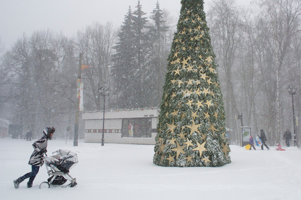 . A woman walks with her child through heavy snowfall at a park in Moscow, Russia, Thursday, Dec. 25, 2014. (AP Photo/Ivan Sekretarev)