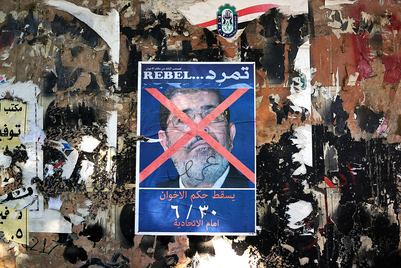 . An anti-President Mohammed Morsi poster is viewed as as thousands of Egyptian protesters celebrate in Tahrir Square as the deadline given by the military to Egyptian President Mohammed Morsi passes on July 3, 2013 in Cairo, Egypt. The president gave a defiant speech last night and vowed to stay in power despite the military threats. As unrest spreads throughout the country, at least 23 people were killed in Cairo on Tuesday and over 200 others were injured. It has been reported that the military has taken over the state television.  (Photo by Spencer Platt/Getty Images)