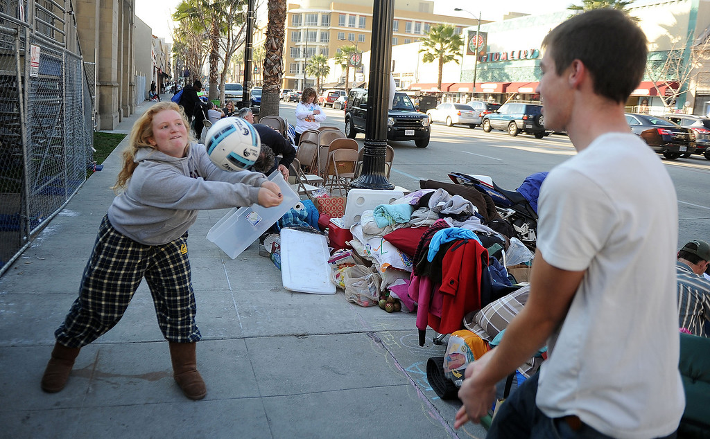 . Sara Ebersole, left, of Napa Valley plays volleyball with Arnaud Caldow of Belgium as they camp out and stake their spots for the Rose Parade along Colorado Boulevard in Pasadena, Calif., on Tuesday, Dec. 29, 2013.     (Keith Birmingham Pasadena Star-News)