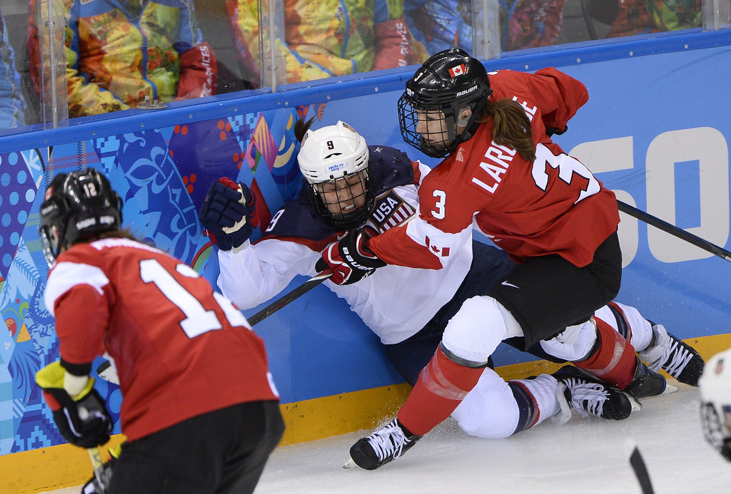 . Canada\'s Jocelyne Larocque (R) hits US Megan Bozek during the Women\'s Ice Hockey Group A match Canada vs USA at the Shayba Arena during the Sochi Winter Olympics on February 12, 2014. AFP PHOTO / JONATHAN  NACKSTRAND/AFP/Getty Images