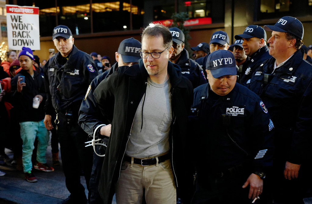 . A man is arrested by police officers after he and other protesters blocked Broadway in front of a McDonald\'s restaurant, Tuesday, Nov. 29, 2016, in New York. About 25 chanting minimum-wage protesters were arrested. They were among about 350 people at a peaceful rally early Tuesday. The event was part of the National Day of Action to Fight for $15. The campaign seeks higher hourly wages, including for workers at fast-food restaurants and airports. (AP Photo/Mark Lennihan)