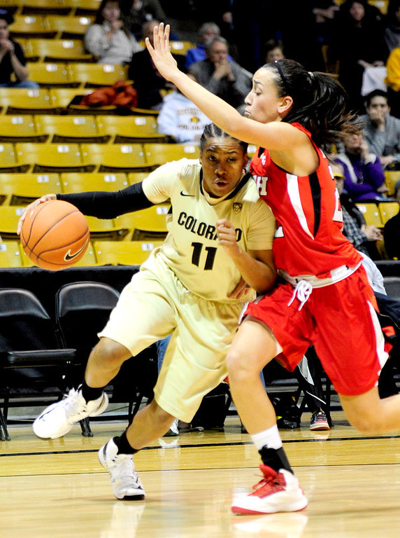 . Colorado\'s Brittany Wilson (left) slides past Utah\'s Danielle Rodriguez (right) for a shot during their basketball game at the University of Colorado in Boulder , Colorado January 8, 2013. BOULDER DAILY CAMERA/ Mark Leffingwell