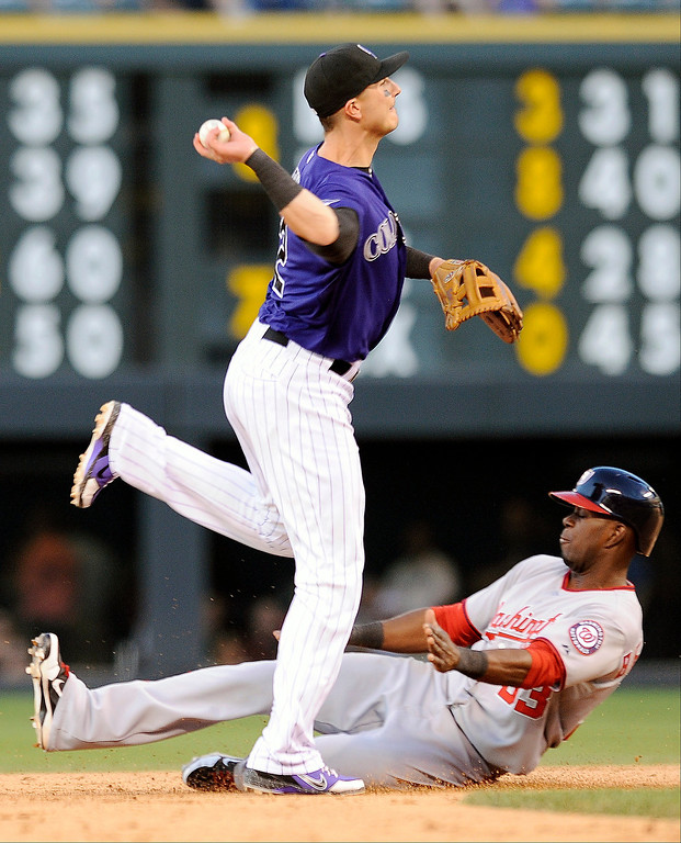 . Colorado Rockies shortstop Troy Tulowitzki throws to first base for the double play as Washington Nationals Roger Bernadina slides into second base in the fifth inning of a baseball game on Tuesday, June 11, 2013 in Denver. (AP Photo/Chris Schneider)