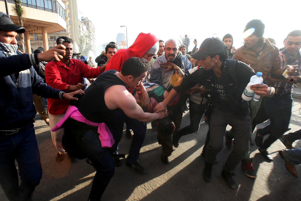 . Protesters evacuate a fatally wounded protester from the scene of clashes in downtown Cairo, Egypt, Saturday, March 9, 2013. (AP Photo/Mohammed Abu Zaid)