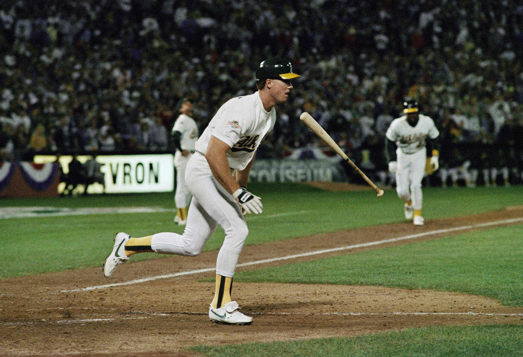 . Oakland A\'s Mark McGwire flips the bat as he runs towards first base after popping out with the bases loaded to end a seventh inning rally in the fourth game of the World Series at Oakland Coliseum, Wednesday, Oct. 19, 1988 . The Dodgers won, 4-3, and now lead the series 3-1. (AP Photo/Rusty Kennedy)