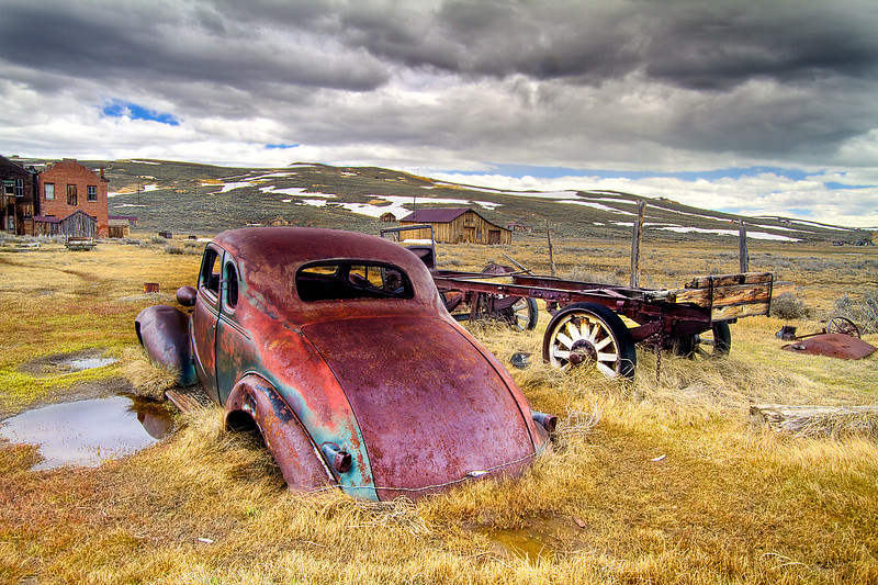 A rusted car disolving away by the hand of time