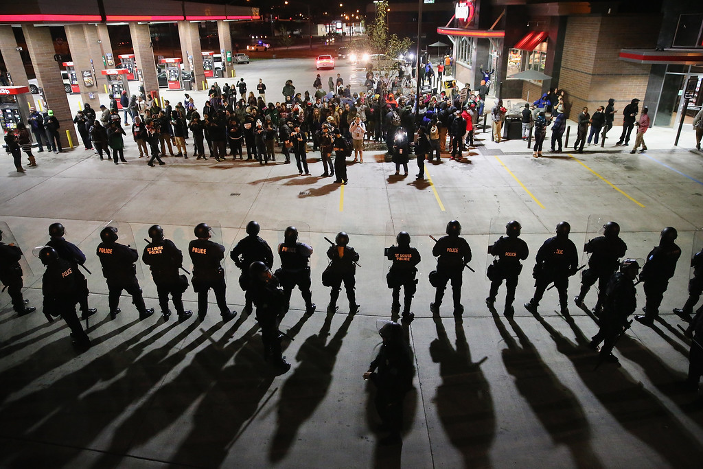 . FERGUSON: Demonstrators protesting the killings of 18-year-olds Michael Brown by a Ferguson, Missouri Police officer and Vonderrit Myers Jr. by an off duty St. Louis police officer are confronted by police wearing riot gear on October 12, 2014 in St Louis, Missouri. The St. Louis area has been struggling to heal since riots erupted in suburban Ferguson following Brown\'s death.  (Photo by Scott Olson/Getty Images)