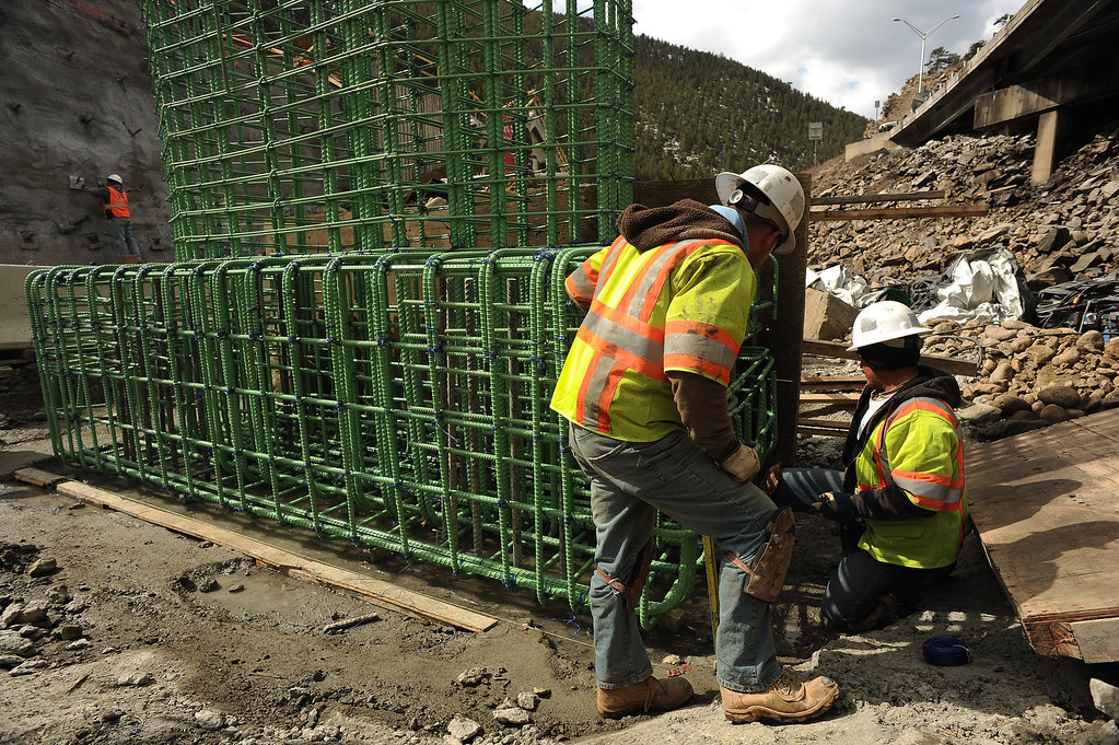 . IDAHO SPRINGS, CO- MARCH 28:  Construction worker Rogelio Dorado, left and Francisco Nicasio, on his knees, work on what will become a new pier for the new bridge east of the twin tunnels.  This bridge will replace the old bridge in the back round which spans over Clear Creek.   Construction continues on road work on I-70 and the twin tunnels near Idaho Springs on March 28th, 2013.  The highway is being widened in the east bound lanes.  The widening will start just west of the twin tunnels after Idaho Springs and will continue until the exit for Highway 6 where I-70 becomes three lanes.  They expect the project to be finished by the end of 2013.  (Photo By Helen H. Richardson/ The Denver Post)