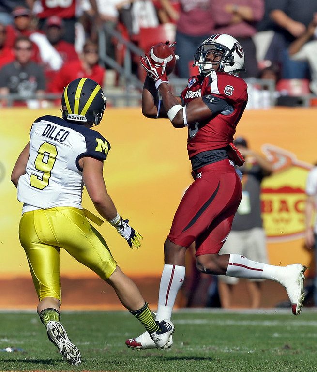 . South Carolina cornerback Jimmy Legree (15) intercepts a pass intended for Michigan wide receiver Drew Dileo (9) during the first quarter of the Outback Bowl NCAA college football game, Tuesday, Jan. 1, 2013, in Tampa, Fla. (AP Photo/Chris O\'Meara)