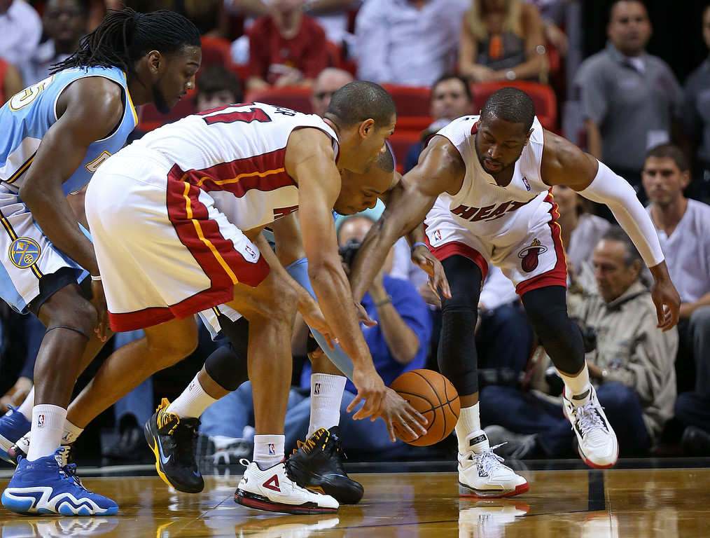 . MIAMI, FL - MARCH 14:  Dwyane Wade #3 and Shane Battier #31 of the Miami Heat fight for a loose ball Randy Foye #4 of the Denver Nuggets during a game  at American Airlines Arena on March 14, 2014 in Miami, Florida. (Photo by Mike Ehrmann/Getty Images)