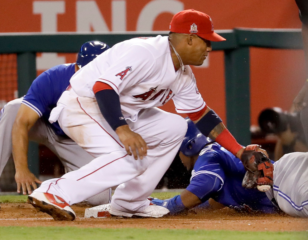 . Toronto Blue Jays\' Edwin Encarnacion, right, is safe at third under the tag by Los Angeles Angels third baseman Yunel Escobar on a single by Jose Bautista during the fourth inning of a baseball game in Anaheim, Calif., Thursday, Sept. 15, 2016. (AP Photo/Chris Carlson)