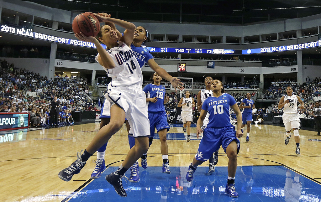 . Connecticut guard Bria Hartley (14) tries to break free from Kentucky guard Janee Thompson, rear, on a drive to the basket in the second half of a women\'s NCAA regional final basketball game in Bridgeport, Conn., Monday, April 1, 2013. Connecticut won 83-53 and advances to the Final Four. (AP Photo/Charles Krupa)