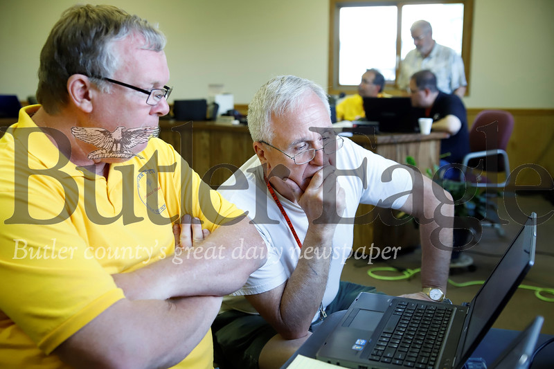 Dale Neely (left) and Julian Savage follow communications on a digital ham radio, capable of translating audio tones into text. Seb Foltz/Butler Eagle