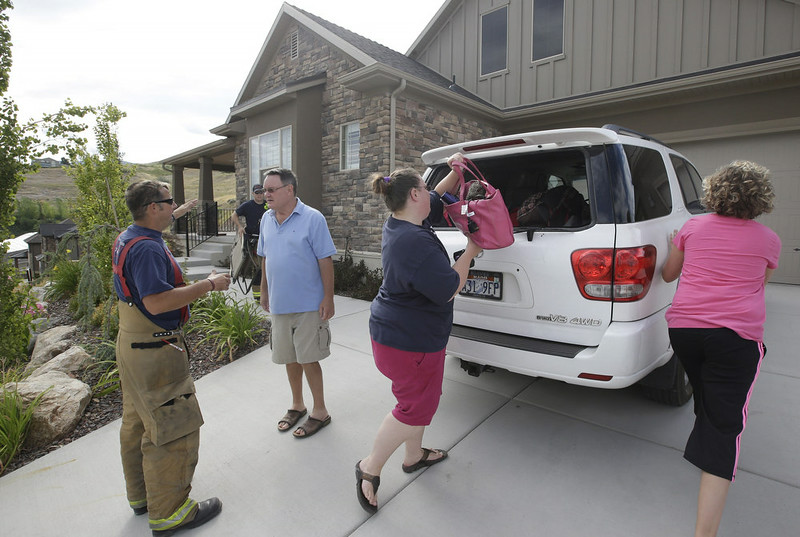 . Home owner Lo Nestman speaks with a fireman as his daughter Mardi Rasch loads their vehicle as they evacuate their home following a landslide in a hillside community of North Salt Lake, Utah, Tuesday, Aug. 5, 2014. North Salt Lake officials say more than 20 homes have been evacuated following an early morning landslide that destroyed one hillside home. (AP Photo/Rick Bowmer)