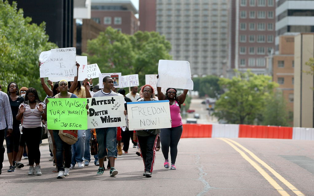 . CLAYTON, MO - AUGUST 20:  Demonstrators protest outside of the Buzz Westfall Justice Center where a grand jury will begin looking at the circumstances surrounding the fatal police shooting of an unarmed teenager Michael Brown on August 20, 2014 in Clayton, Missouri. Brown was shot and killed by a Ferguson, Missouri police officer on August 9. Despite the Brown family\'s continued call for peaceful demonstrations, violent protests have erupted nearly every night in Ferguson since his death  (Photo by Joe Raedle/Getty Images)