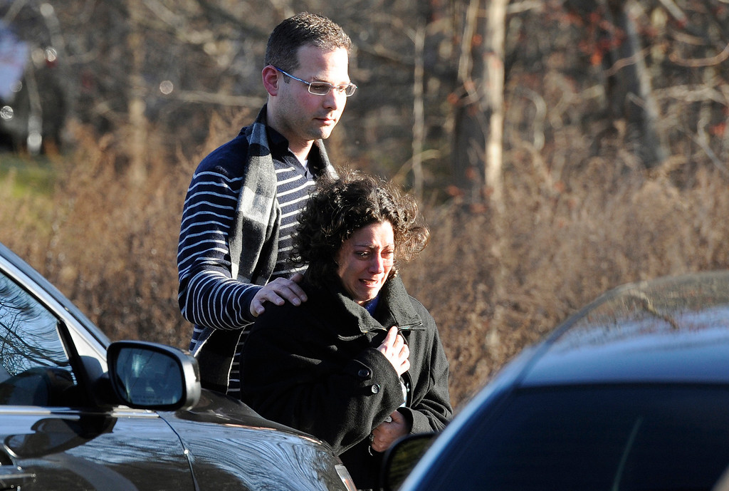 . A man and woman leave the staging area for family around near the scene of a shooting at the Sandy Hook Elementary School in Newtown, Conn., about 60 miles (96 kilometers) northeast of New York City, Friday, Dec. 14, 2012. An official with knowledge of Friday\'s shooting said 27 people were dead, including 18 children.  (AP Photo/Jessica Hill)
