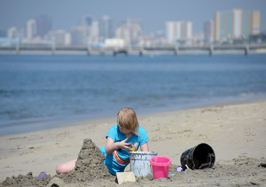 . Children had a chance to hone their sand castle building skills in a sand castle camp Monday at Granada Beach in Belmont Shore. Shelby Randall works on her creation as the sun begins to emerge from clouds to reveal the city\'s skyline. 20130805 Photo by Steve McCrank / Staff Photographer