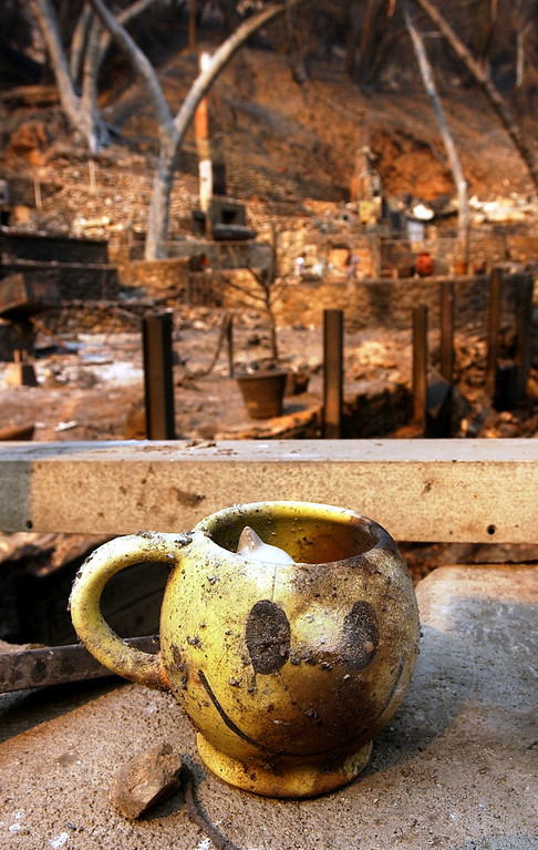 . The GrandPrix fire started three days before the Old Fire.  It fed into the Old Fire. Ten years later, there are rumblings that it too was started by an arsonist. But to this day, its origins remain a mystery. Debbie Dey\'s scorched coffee mug sits among the ruins of her burned down home in Palmer Canyon, Tuesday, Oct. 28, 2003, in Claremont. (Staff photo by Will Lester/Inland Valley Daily Bulletin)