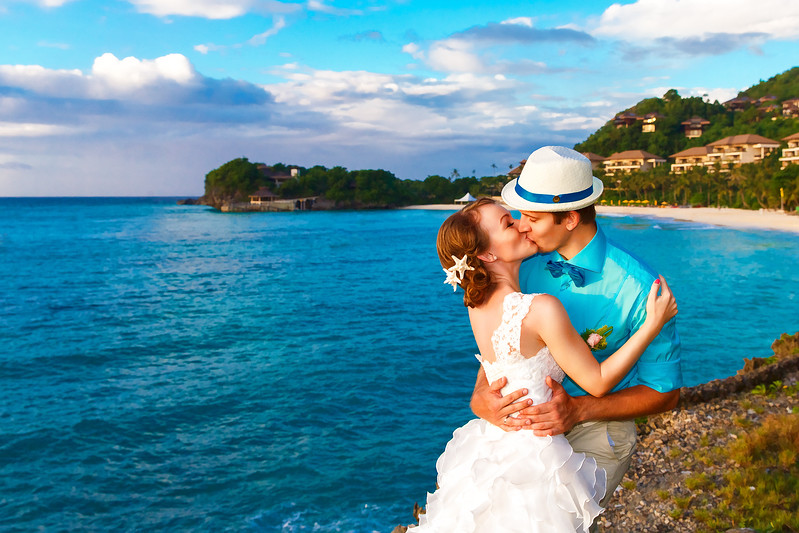 Wedding. Bbride and groom kissing on the tropical coast at sunset
