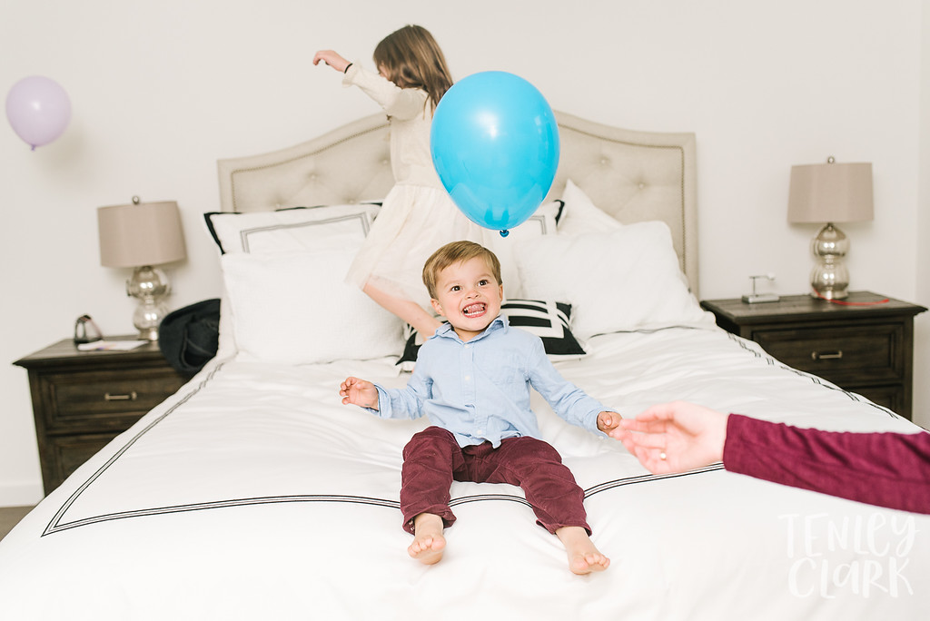 Kids playing with balloons on bed. Lifestyle in-home family photoshoot in Marin, CA by Tenley Clark Photography.