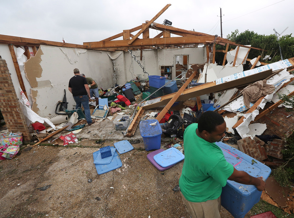 . People help to start cleaning up and salvage items from a home that was destroyed by a tornado in Cleburne, Texas, Thursday, May 16, 2013. (AP Photo/LM Otero)