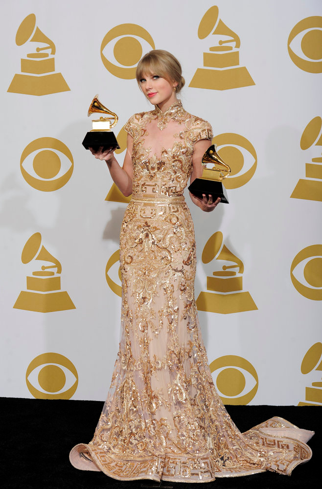 ". Taylor Swift poses backstage with the awards for best country song and best country solo performance for ""Mean\"" at the 54th annual Grammy Awards, Monday, Feb. 13, 2012, in Los Angeles. (AP Photo/Mark J. Terrill)"