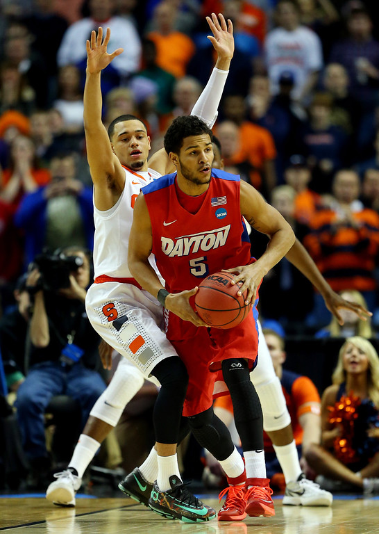 . BUFFALO, NY - MARCH 22:  Devin Oliver #5 of the Dayton Flyers looks to pass as Tyler Ennis #11 of the Syracuse Orange defends during the third round of the 2014 NCAA Men\'s Basketball Tournament at the First Niagara Center on March 22, 2014 in Buffalo, New York.  (Photo by Elsa/Getty Images)