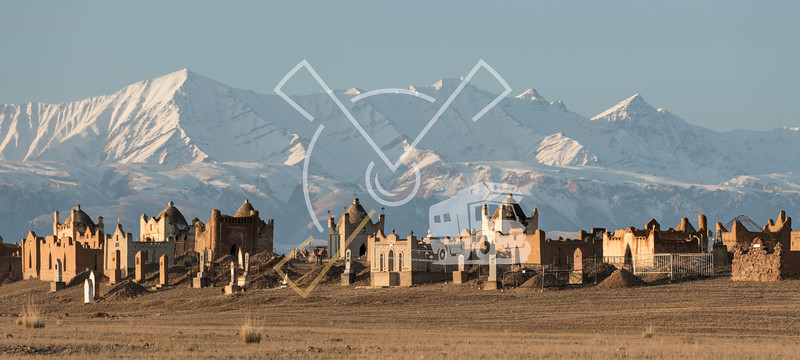 first morning sunlight falling on the cemetery of Terek, south of Baetov, near the Mels-Ashu pass with the amazing landscape of the  Tian Shan mountains covered in snow around