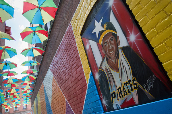 07/03/19 Wesley Bunnell | Staff An alleyway on Arch St, directly adjacent to Criollisimo Restaurant, is decorated with hanging umbrellas and colorful paintings.
