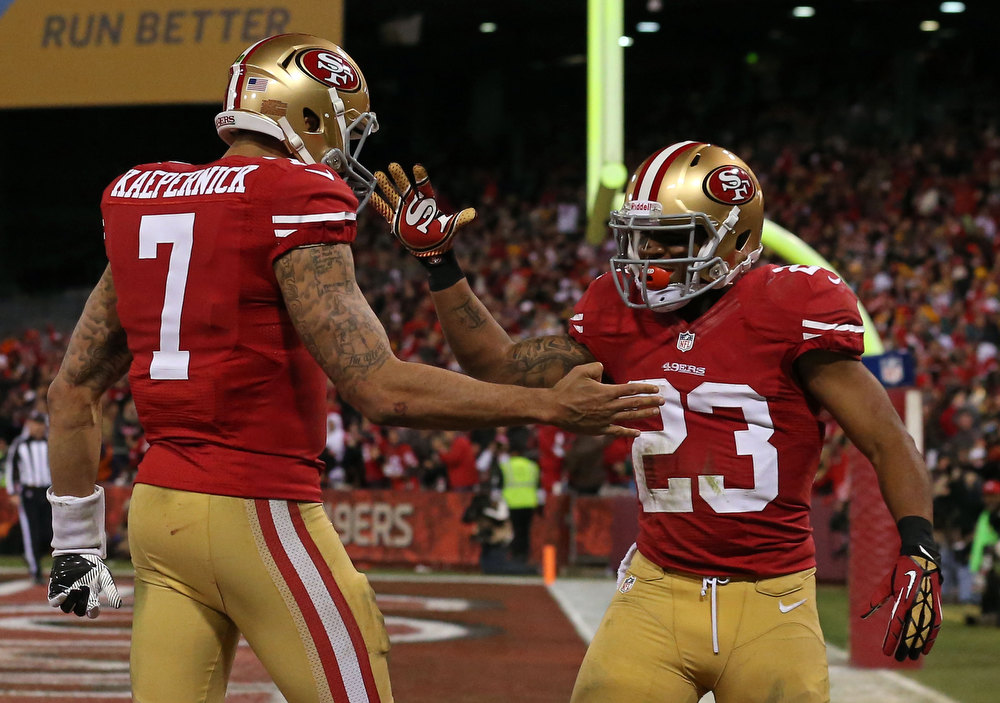 Description of . Quarterback Colin Kaepernick #7 of the San Francisco 49ers celebrates with running back LaMichael James #23 after running the ball for a touchdown against the Green Bay Packers in the third quarter during the NFC Divisional Playoff Game at Candlestick Park on January 12, 2013 in San Francisco, California.  (Photo by Stephen Dunn/Getty Images)