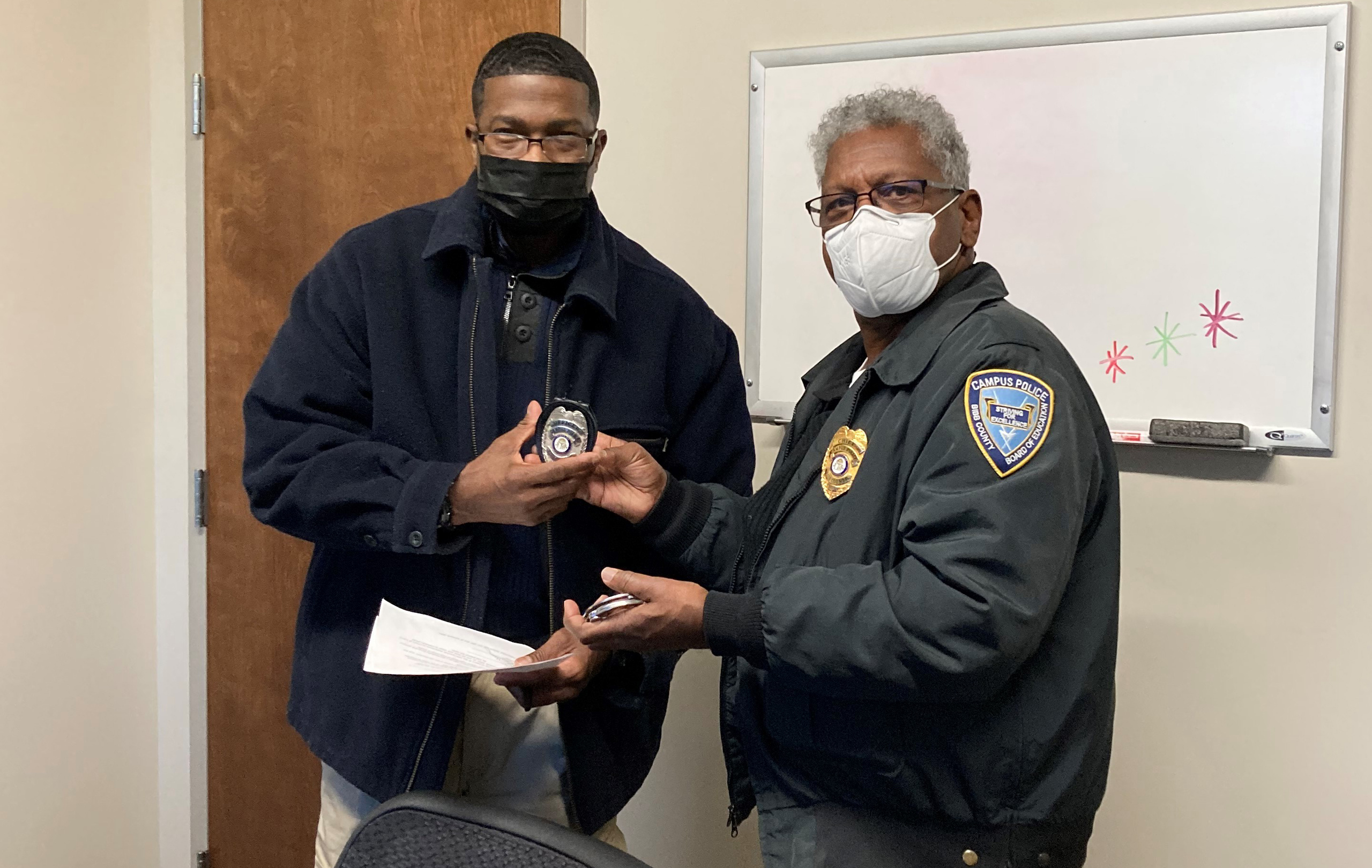 Russell Bentley (pictured right) presents a new officer his police badge after taking the Georgia Peace Officer's Oath of Office.