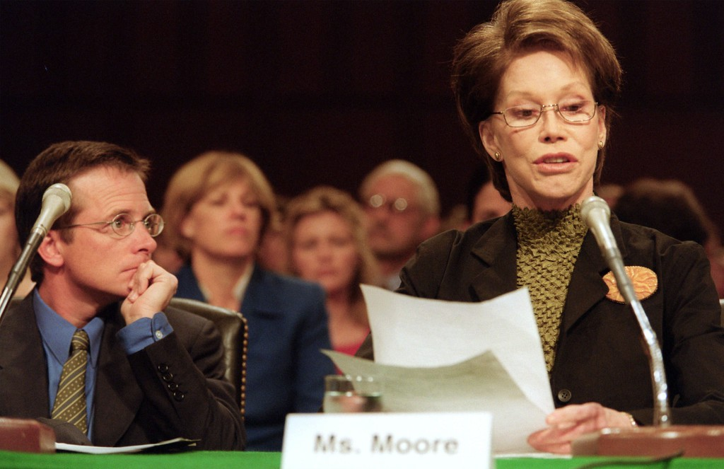 . Actor Michael J. Fox looks on as actress Mary Tyler Moore testifies on Capitol Hill Thursday, Sept. 14, 2000, before a Senate Appropriations subcommittee hearing on stem cell research. They urged the subcommittee to release federal funding for research involving embryonic stem cells, which they said could lead to cures for diseases such as Parkinson\'s, juvenile diabetes and Alzheimer\'s. (AP Photo/Kamenko Pajic)